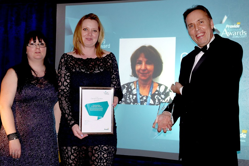 Colleagues collecting the award on behalf of Caroline, Caroline on the screen, John Niland Chief Executive